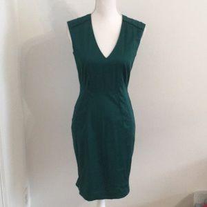 Emerald green low v-neck sheath dress.